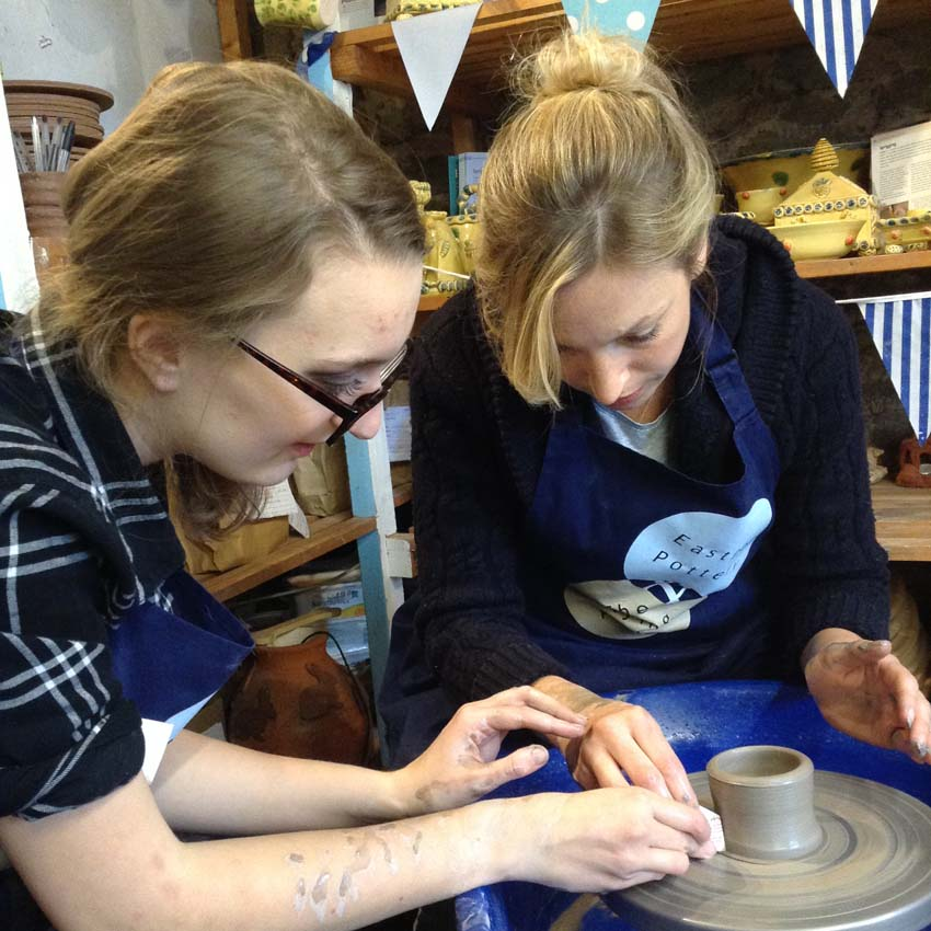 Aimee one of our community arts aprentices showing a customer how to make a pot on the potter's wheel
