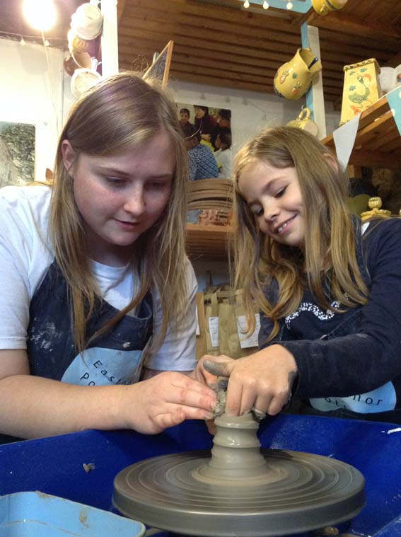 Immy one of our community arts aprentices showing a girl how to make a pot on the potter's wheel
