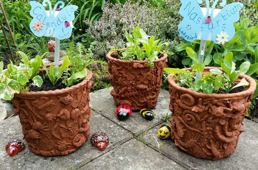 collaborative planters made by bishops cleeve primary school and eastnor pottery and the flying potter