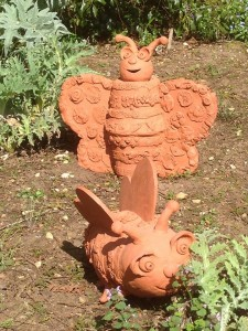 collaborative terracotta bee and snail made by oxfordshire primary school children