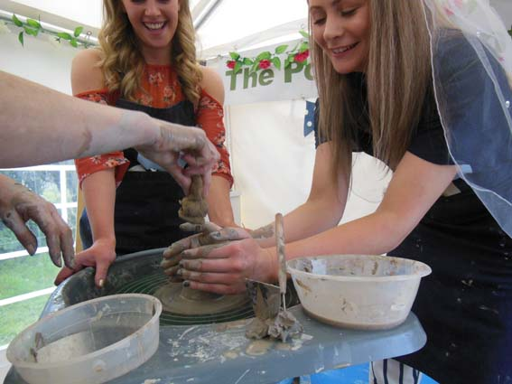 bride to be makes a pot on the potters wheel at  pottery hen party