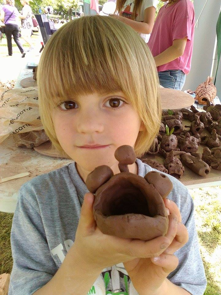 child showing his clay fish made at hellens garden festival 2018