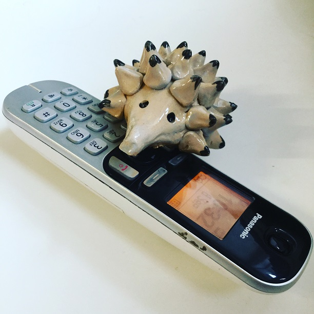 hand made pottery hedgehog on the phone