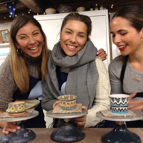 City girls make pottery on the potter's wheel in herefordshire