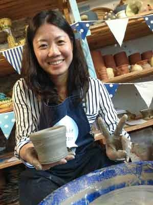 workshop participant at eastnor pottery proud of her pot made on the potter's wheel