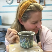 hen party participant paintes her freshly thrown pot made on the potter's wheel