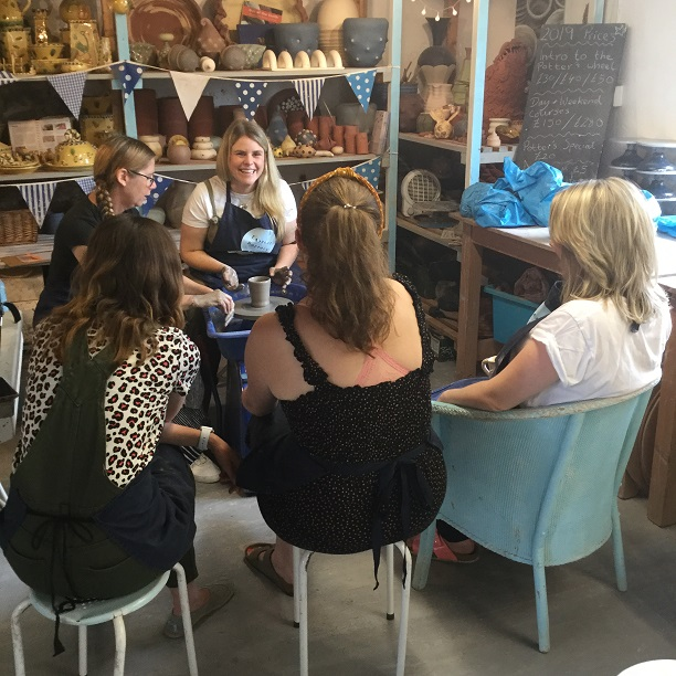yummy mummies enjoy watching each other make a pot on the potter's wheel at eastnor pottery in herefordshire
