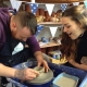 couple watch each other make a pot on the potter's wheel at eastnor pottery herefordshire