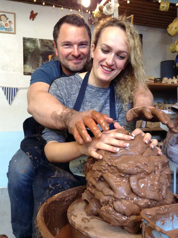 pottery workshop participants sharing the potter's wheel and a huge lump of clay at eastnor pottery west midlands