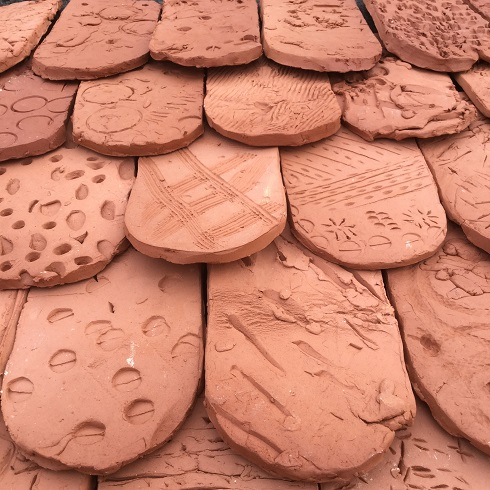 textured terracotta tiles made by young children at washwood heath nursery school and jon the potter from eastnor pottery and the flying potter