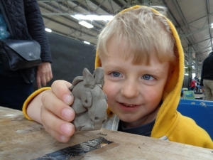 boy and his hand made clay unicorn made wit the flying potter at countrytastic