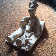 sun bathing clay model figure reclining on a beach towl made at eastnor pottery and the flying potter