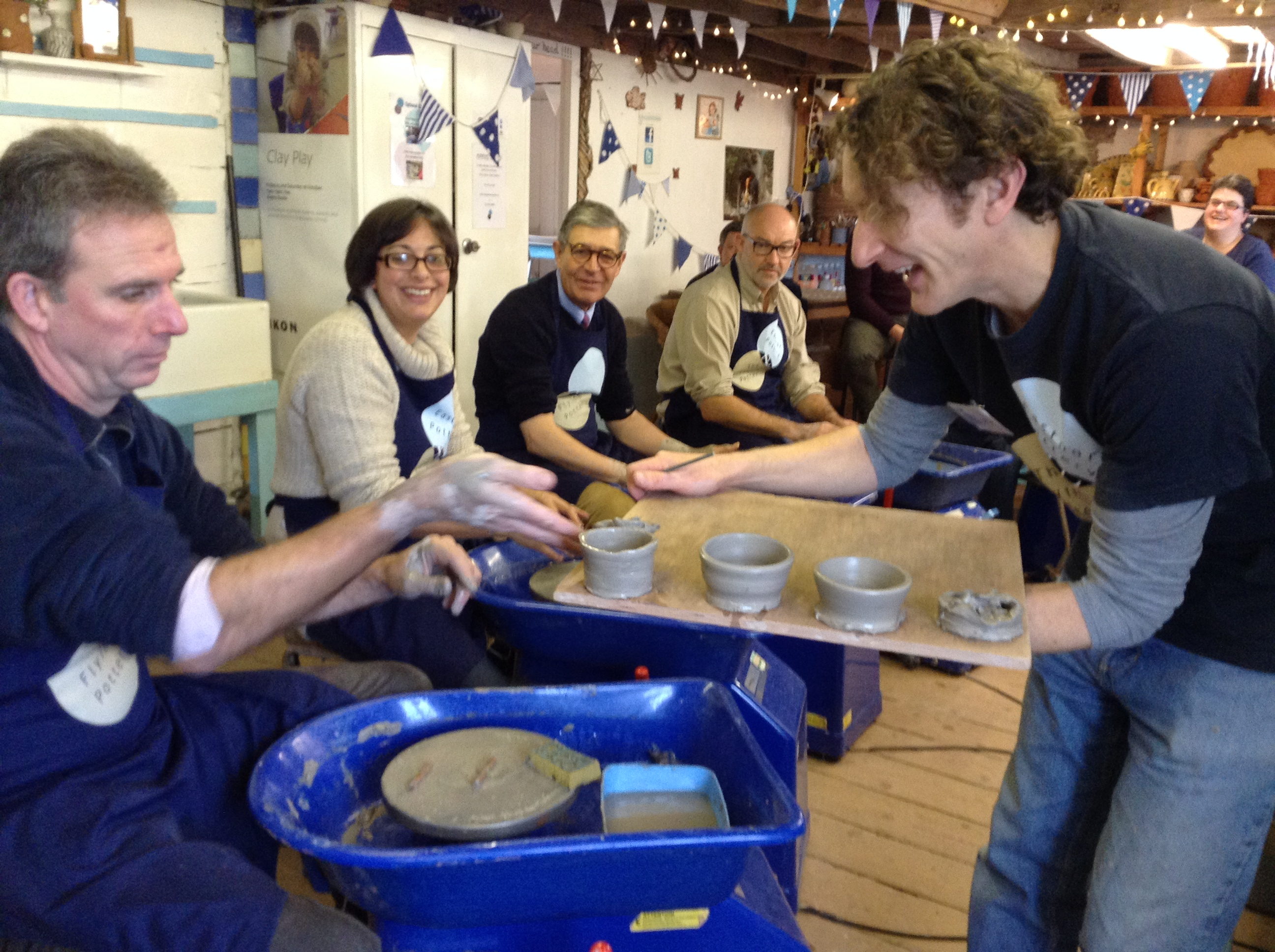 work colleagues makeing pottery on the potter's wheel at eastnor pottery
