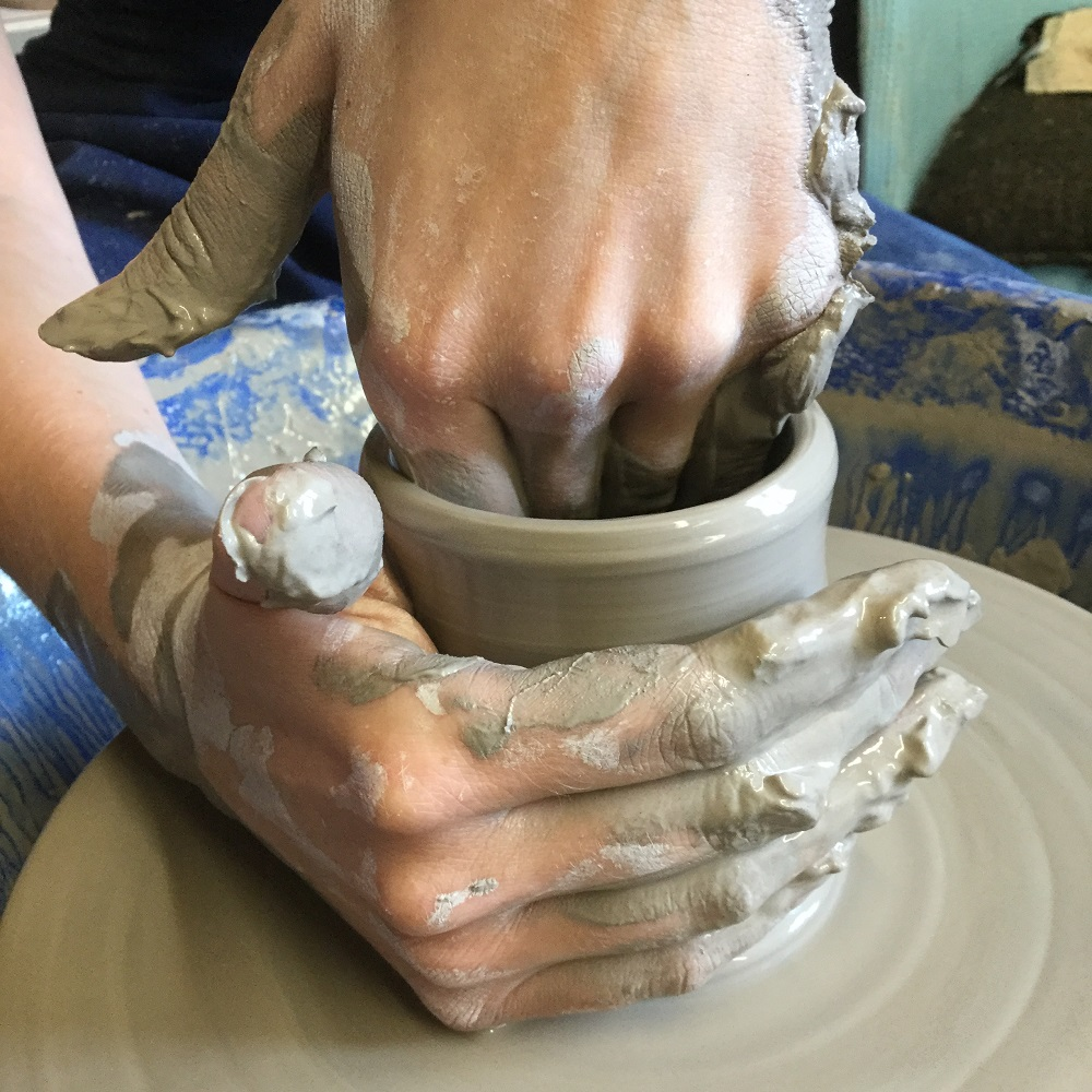 close up of clay covered hands on the potter's wheel at eastnor pottery