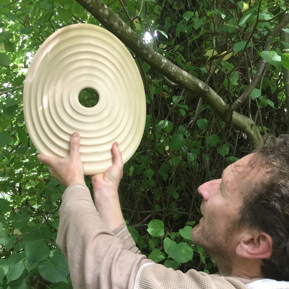 herefordshire ceramic artist jon williams hanging his percusive ceramic disks at hellens garden festival in herefordshire