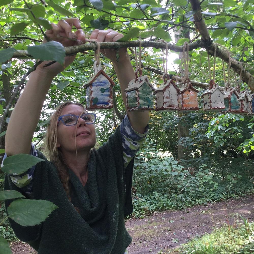herefordshire potter sarah monk hanging her ceramic bug houses at hellens garden festival