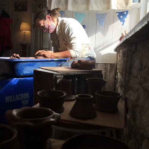 aspiring potter learning to make pots on the wheel at eastnor pottery herefordshire
