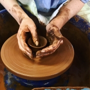 pottery course participant at eastnor pottery cupping a spinning clay pot