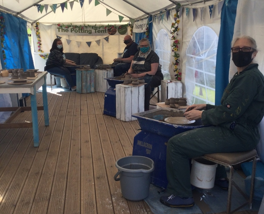 potters wheel course participants inside the potting tent at eastnor pottery