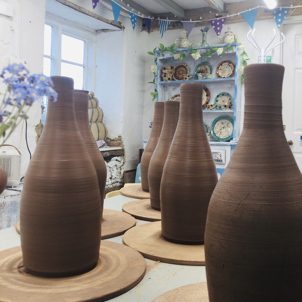 thrown terracotta bottles lined up and drying in pottery studio