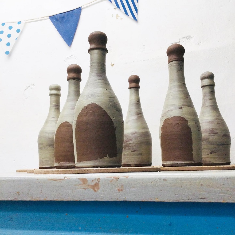 hand thrown terracotta bottles painted with white slip on table