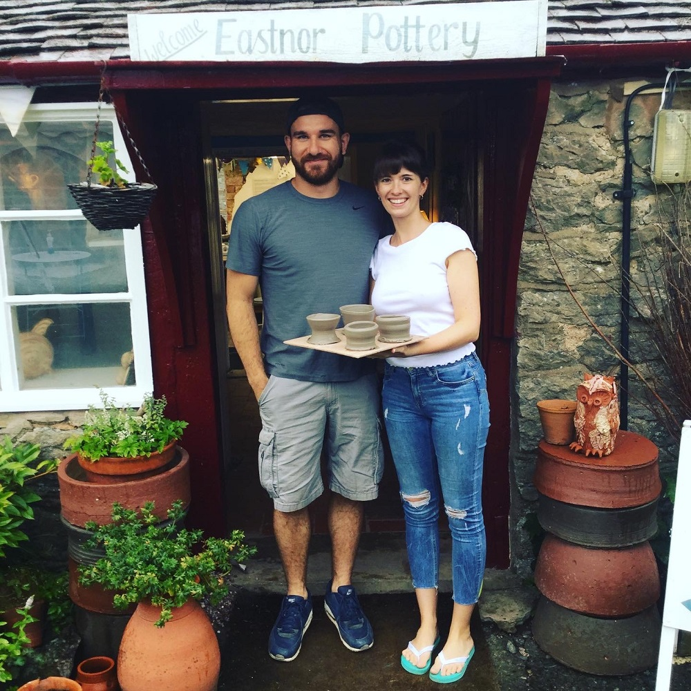 honeymoon couple who took part in a potter's wheel introduction standing outside pottery