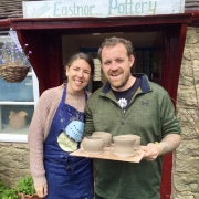 couple standing in doorway of pottery holding pots made at eastnor