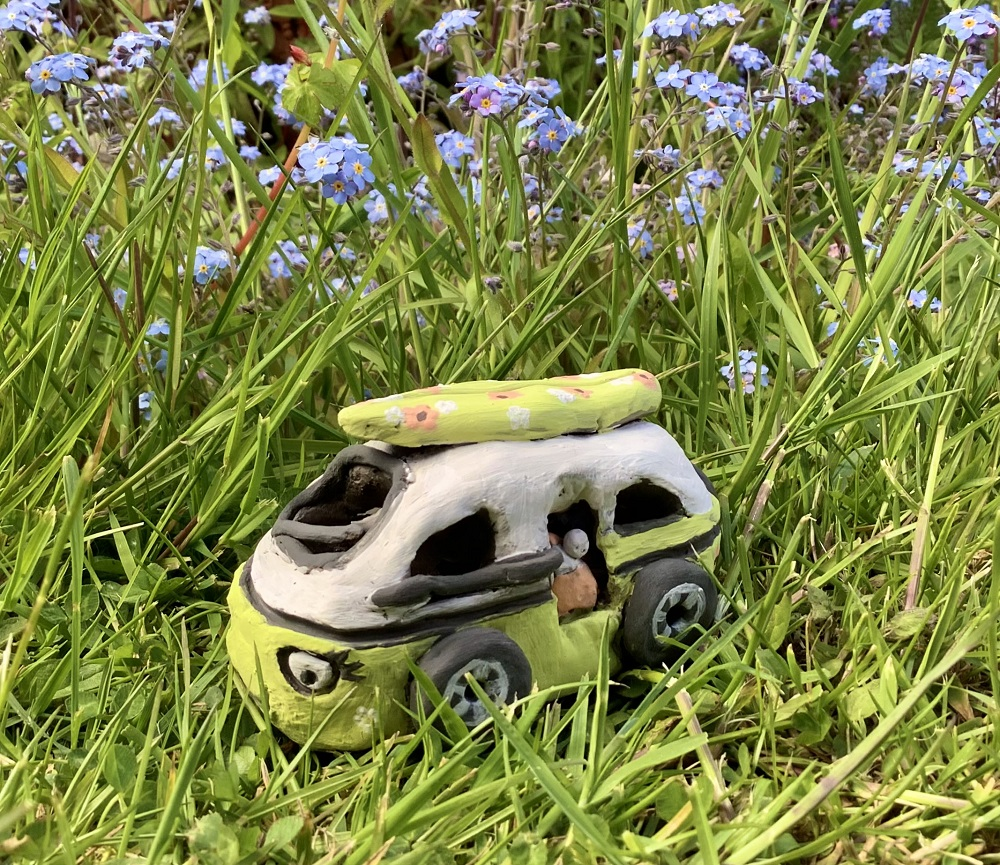 clay handmade campervan painted green on grass with flowers in the background
