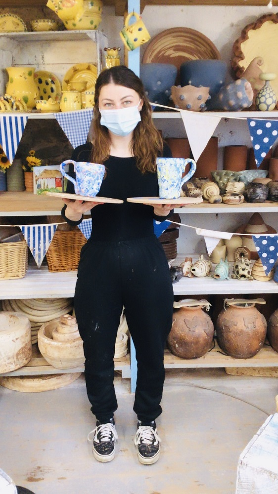 lady holding mugs made on weekend pottery course in the pottery studio