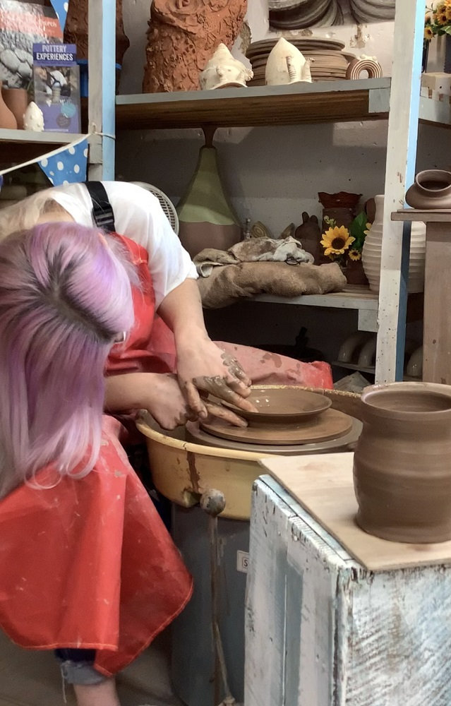 lady throwing plate on weekend pottery course leaning over to throw