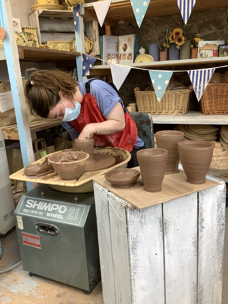 lady throwing pot on weekend pottery course surrounded by pots she had thrown previously