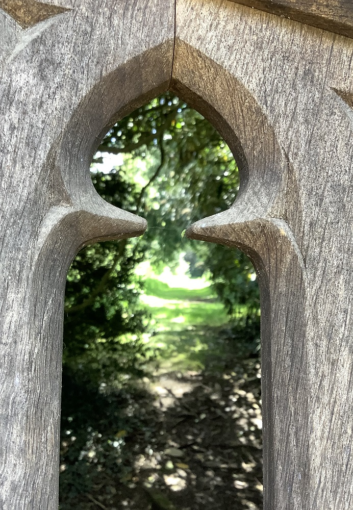 wooden castle gate with a woodland path behind