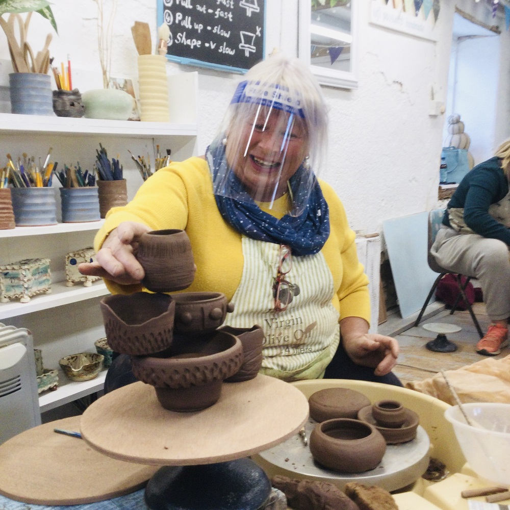 lady participating in pottery weekend course placing her pots in display
