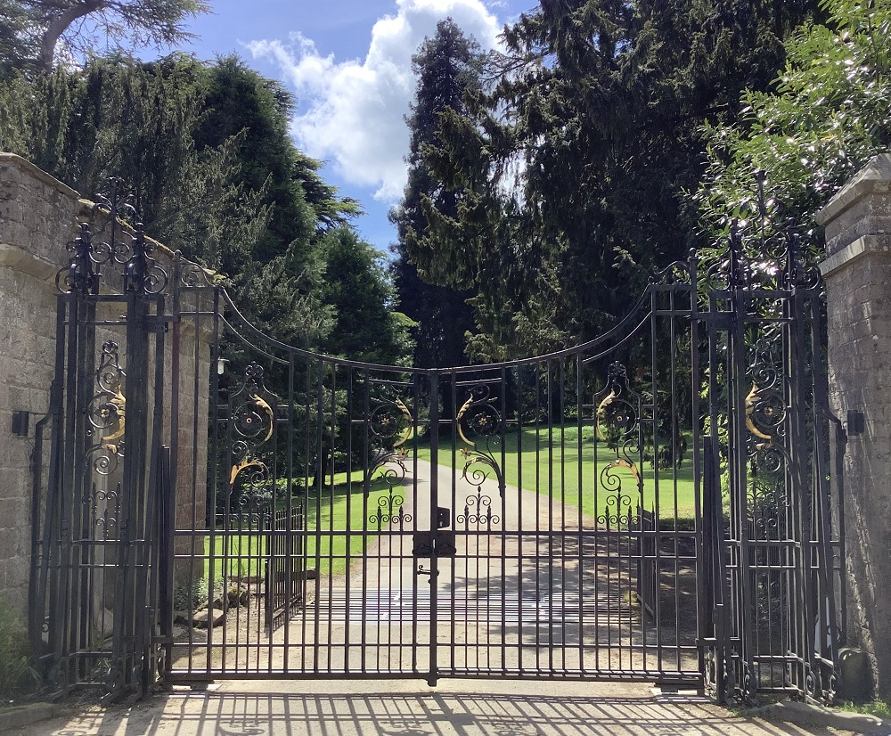 black and gold gates leading to eastnor castle with driveway path behind