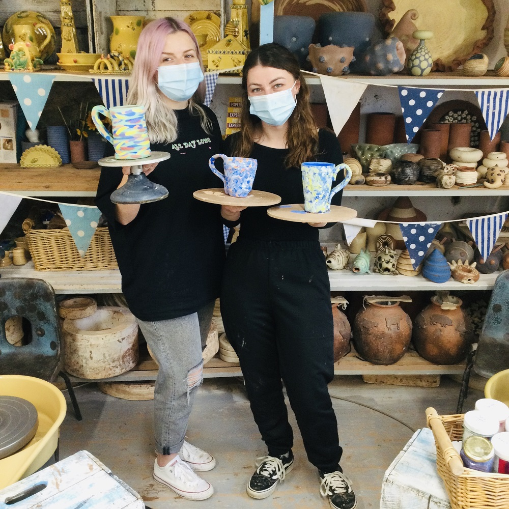 two best friends taking part on weekend pottery course holding pots they made in the pottery studio