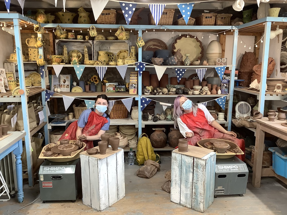 two friends taking part in pottery weekend course on their wheels throwing pots