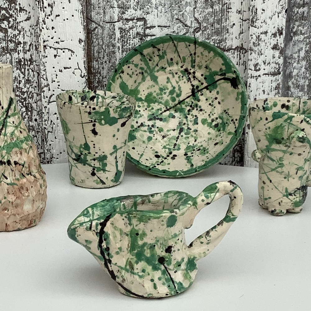 selection of pots and plates painted white and splattered with shades of green and blue