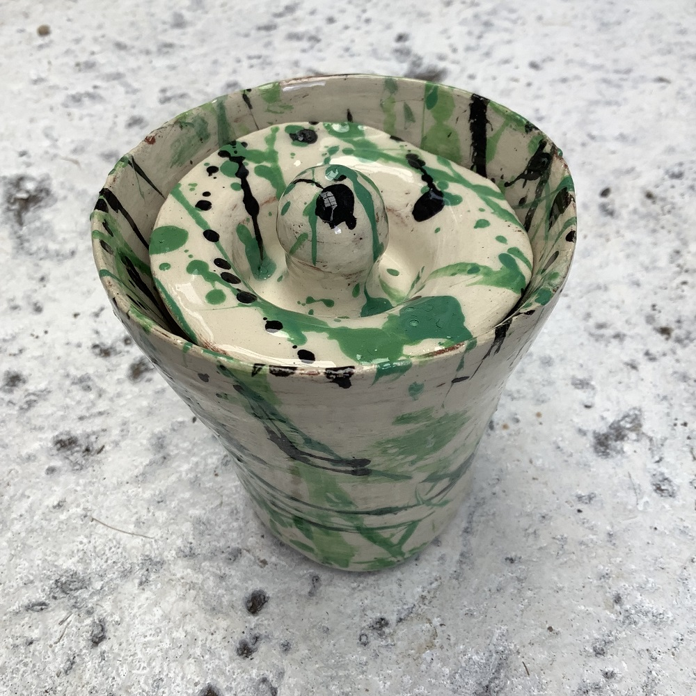 pot with a lid painted white with green and blue splatters