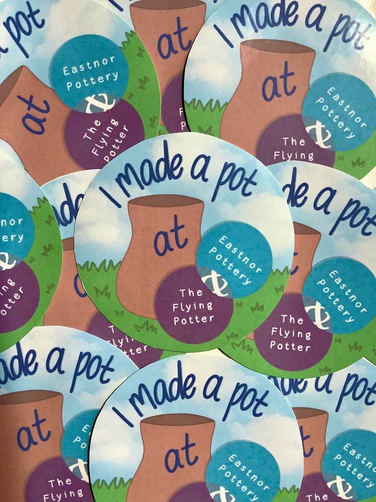 round stickers with the words 'I made a pot at Eastnor Pottery' with Eastnor Pottery logo, in a pile of the same designed stickers