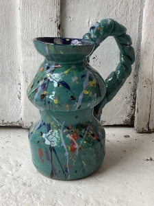 curve shaped jug with textured handle, painted teal and decorated with splattered paint