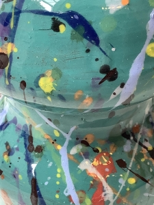 up close image of ceramic teal and decorated with splattered paint