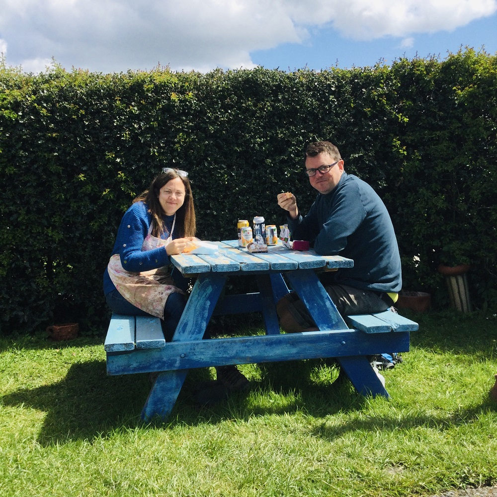 man and woman couple eating lunch on blue bench outside
