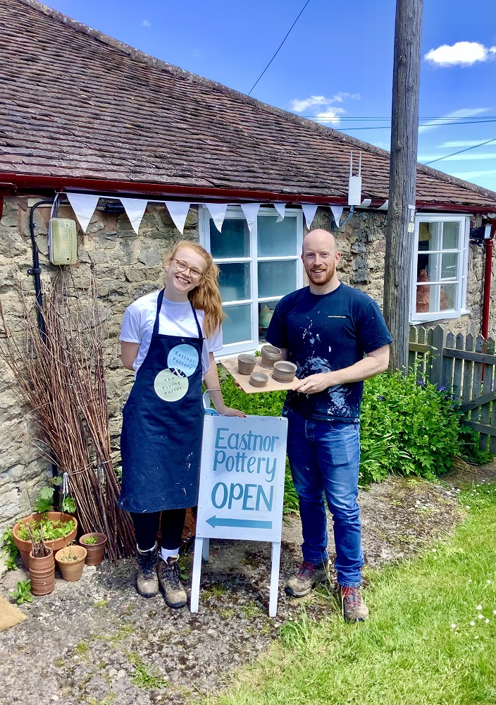 man and woman couple standing outside eastnor pottery next to sign holding pots and wearing eastnor pottery aprons