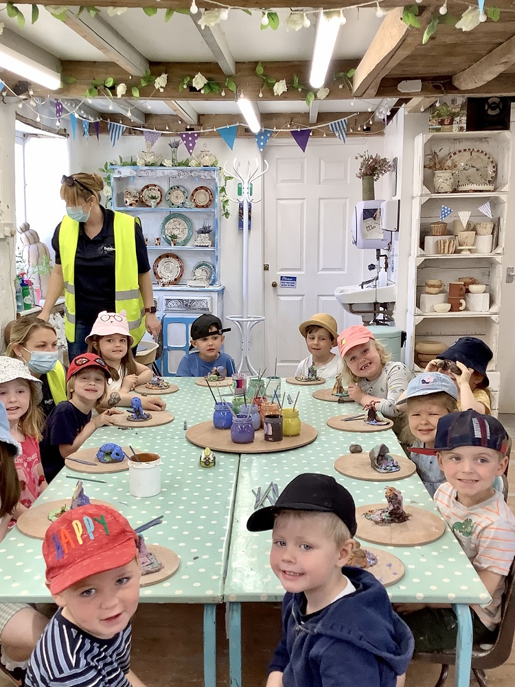 group of children sat around table taking part in a hand clay modelling session