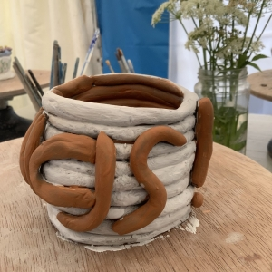 coil pot painted white with brown letters spelling part of the word 'things'