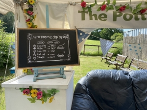 black chalk bard style poster reading 'eastnor's step by step' inside a white marque, on a white table next to a blue sofa which greenery outside