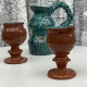 two terracotta goblets in front of a large teal and splatter decorated jug