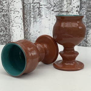 terracotta goblets, one laying flat the other up right, painted teal inside