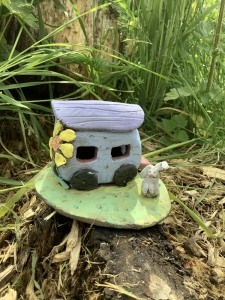 purple camper van with a yellow flower on the side, with a green base and white rabbit, hand modeled with clay