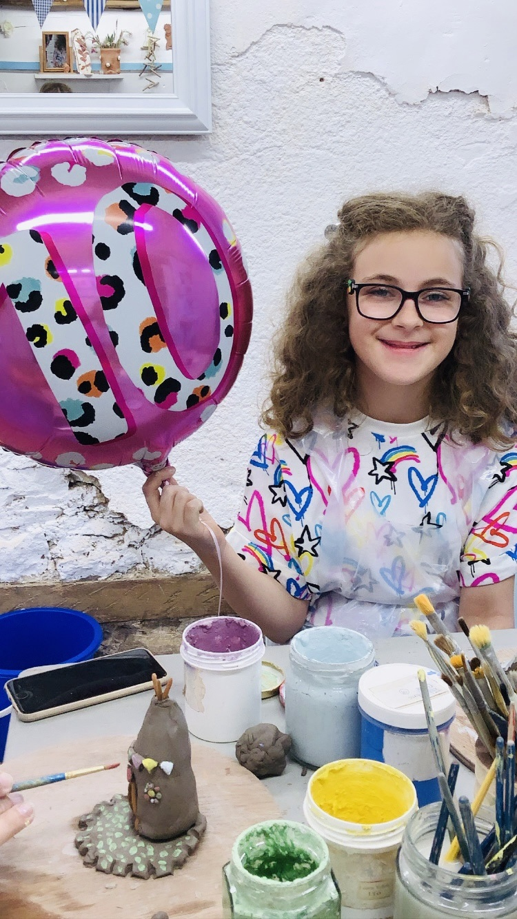 child holding pink 10th birthday baloon next to clay creation made at eastnor pottery